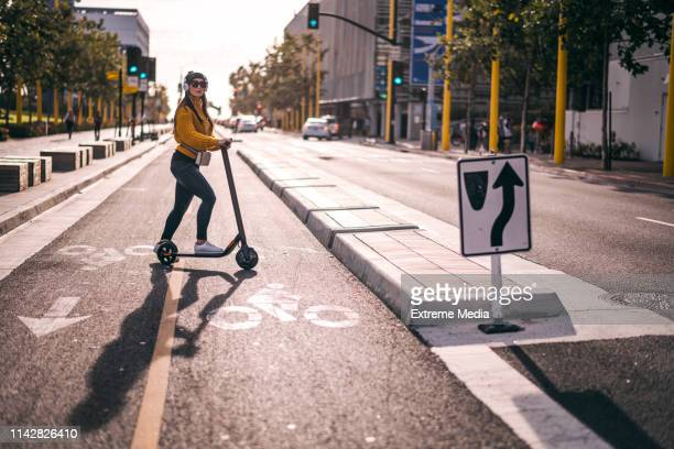 an urban woman listening to music over the headphones looking to join the traffic in the city street downtown - mobility scooter stock photos and pictures