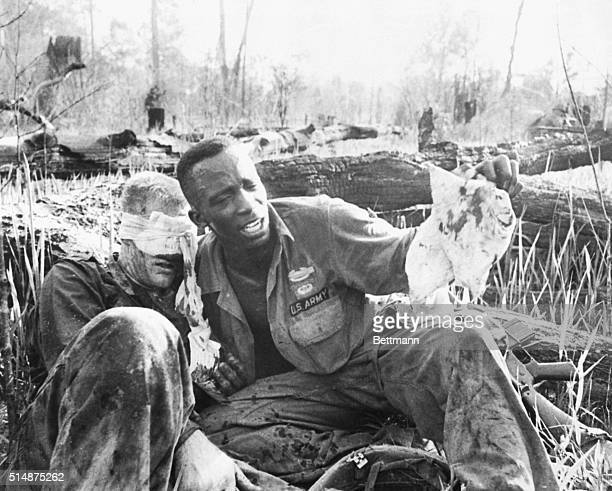 An US Army medic tries to help a wounded soldier in Vietnam