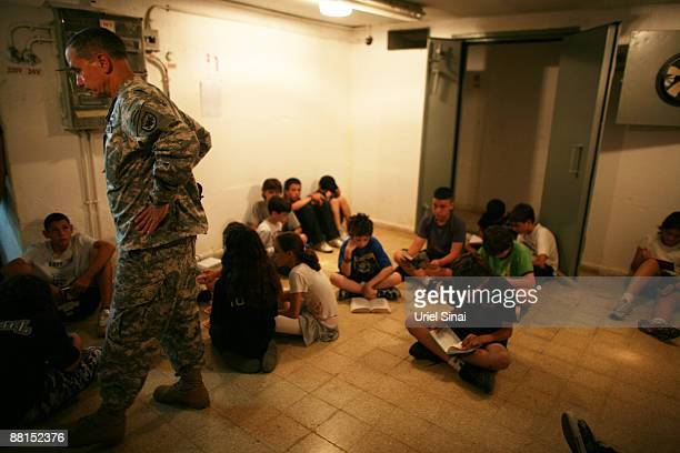 An U.S army representative joins school children in a boom shelter during a Home Front Command national exercise in a school on June 02, 2009 in Tel...
