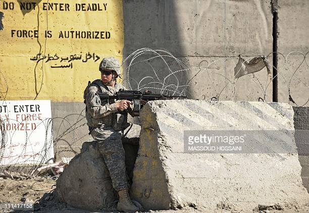 An US army soldier guards at the site of a suicide attack in the main gate of US military base Camp Phoenix in Kabul on Apirl 2 2011 Several...