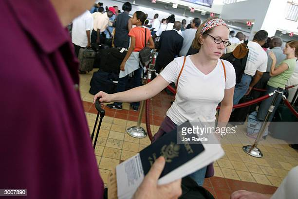 An US citizen waits in line to get her American Airlines boarding pass as she prepares to leave February 23 2004 in PortauPrince Haiti 50 US Marines...