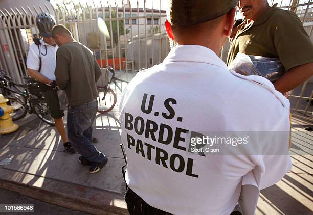 An US Customs and Border Protection bike patrol agent assists Mexican's being returned to Mexico after they were apprehended for entering the United...