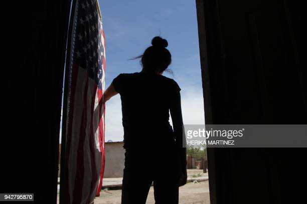 An US flag hangs from the door of the house of a Mexican woman who looks towards the border line between Mexico and the United States in Ciudad...