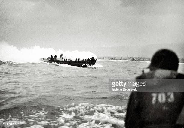 An US landing craft is approaching Omaha Beach 6th June 1944 It is covered with thick white smoke Barbed wire installations can be seen along the...