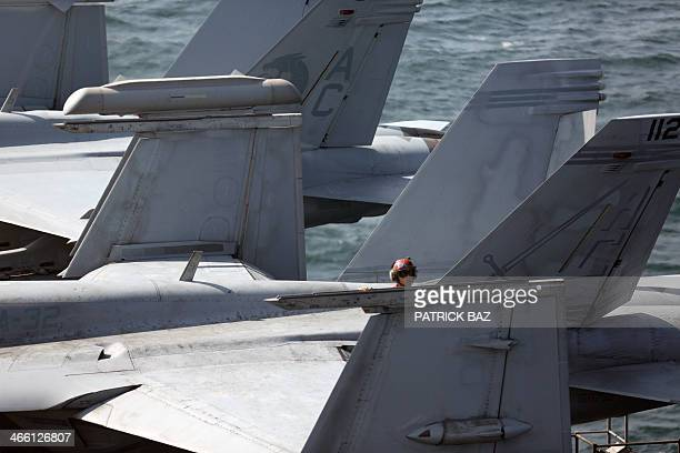 An US Navy Brown Shirt aka Air Wings Plane Captain checks the wing of an F18 fighter jet parked on the deck of the USS Harry STrumann in the Gulf of...