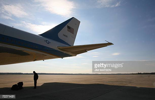 An US Secret Service Agent waits under the tail section of Air Force One at Andrews Air Force Base, Maryland, 26 October 2006 as US President George...