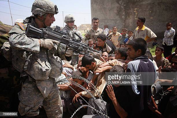 An US soldier gestures with his M249 SAW as Iraqis rush to receive humanitarian aid from the Iraqi Ministry of Trade in Mufrek western Baquba 60 kms...