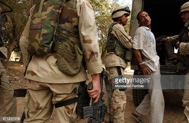 An US soldier loading a handcuffed man into a truck Baghdad Iraq 2003
