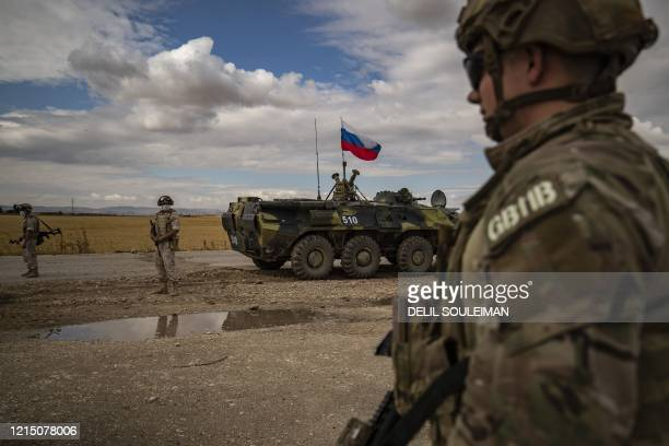 An US soldiers stand next to a Russian military vehicle along the M4 highway by the town of Tal Tamr on May 25 as they monitor the reopening of the...