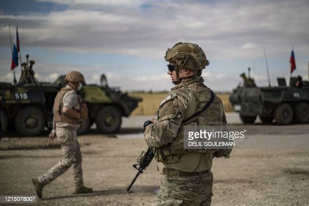 An US soldiers stand next to Russian military vehicles along the M4 highway by the town of Tal Tamr on May 25 as they monitor the reopening of the...