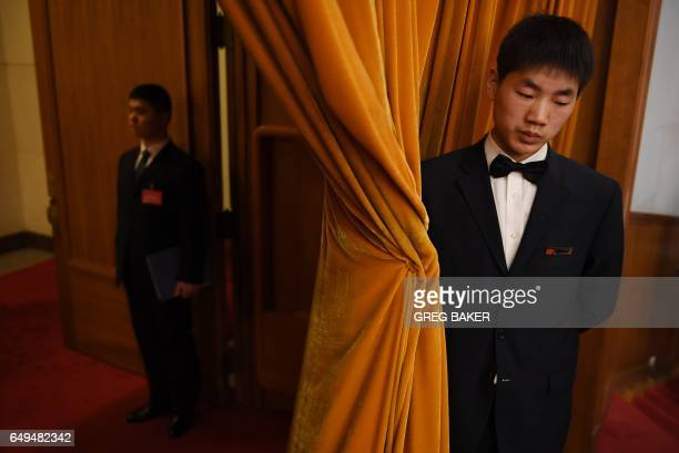 An usher and security guard stand at an entrance during the 2nd plenary session of the National People's Congress in Beijing's Great Hall of the...