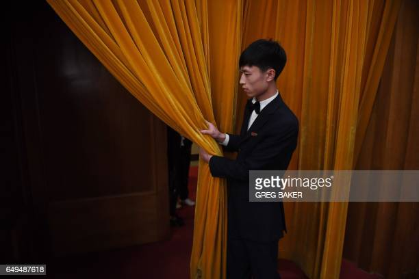 An usher holds a curtain at an entrance during the 2nd plenary session of the National People's Congress in Beijing's Great Hall of the People on...