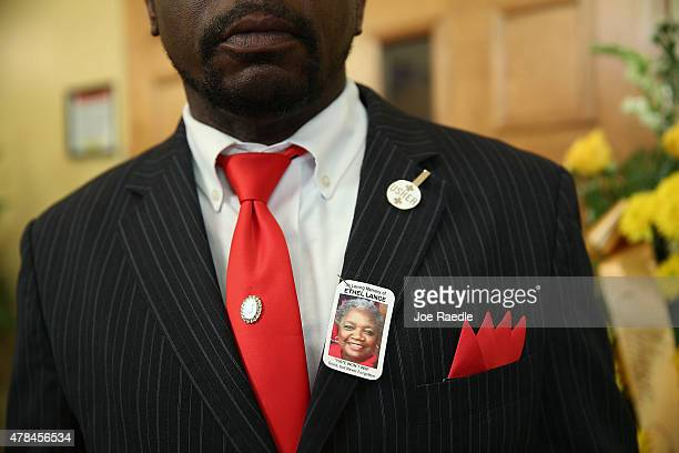 An usher wears a picture of Ethel Lance who was one of nine victims of a mass shooting at the Emanuel African Methodist Episcopal Church as they...