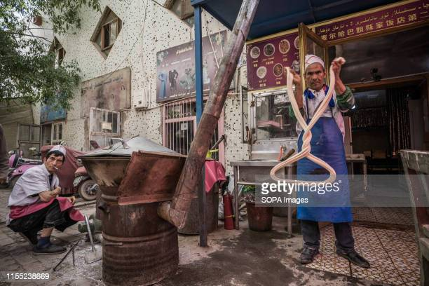 An Uyghur man makes noodles at the Kashgar bazaar The Xinjiang province is located in the North Western part of China it is the largest province in...