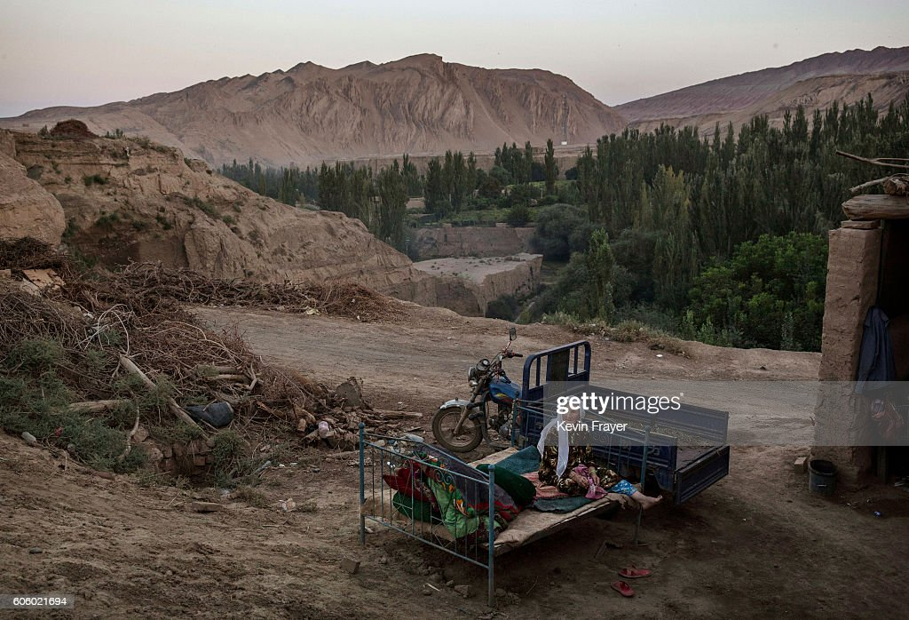 An Uyghur woman sits on a bed outside as she waits for relatives to arrive for a holiday meal during the Corban Festival on September 12, 2016 in Turpan County, in the far western Xinjiang province, China. The Corban festival, known to Muslims worldwide as Eid al-Adha or 'feast of the sacrifice', is celebrated by ethnic Uyghurs across Xinjiang, the far-western region of China bordering Central Asia that is home to roughly half of the country's 23 million Muslims. The festival, considered the most important of the year, involves religious rites and visits to the graves of relatives, as well as sharing meals with family. Although Islam is a 'recognized' religion in the constitution of officially atheist China, ethnic Uyghurs are subjected to restrictions on religious and cultural practices that are imposed by China's Communist Party. Ethnic tensions have fueled violence that Chinese authorities point to as justification for the restrictions.