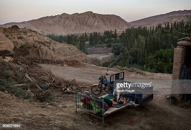 An Uyghur woman sits on a bed outside as she waits for relatives to arrive for a holiday meal during the Corban Festival on September 12 2016 in...