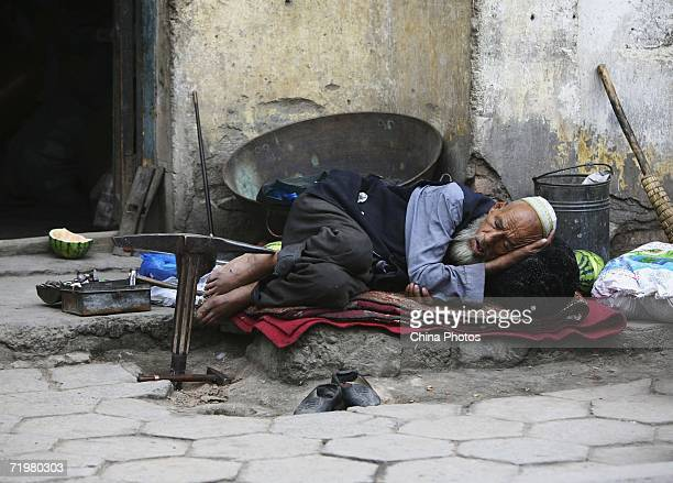 An Uygur smith takes a nap on his booth in a street on September 21, 2006 in Kashi of Xinjiang Uygur Autonomous Region, northwest China. Kashi is an...