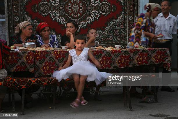 An Uzbek girl attends a wedding where traditional carpets adorn the tables and walls August 13 2006 in Oykabura village in the Fergana Valley region...