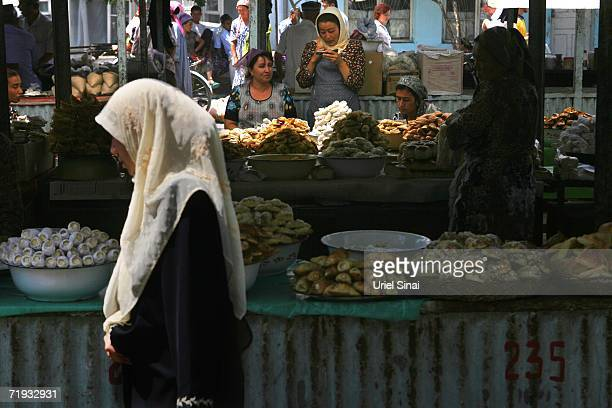 An Uzbek woman passes a stall selling sweet pastries in the local produce market August 13 2006 in Margilan in the Fergana Valley region in the...