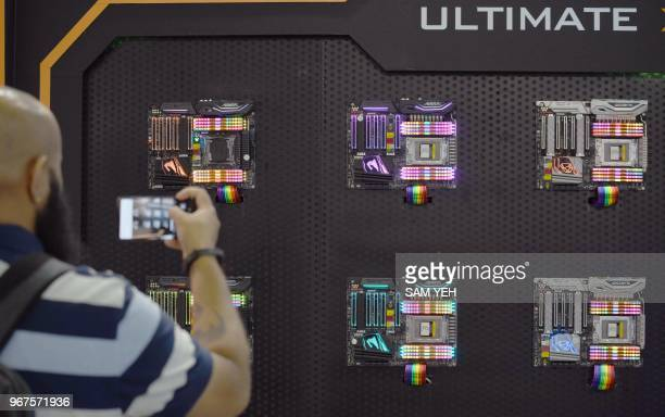 An visitor takes a picture of the decorated LED computer motherboards during Computex 2018 at the Nangang Exhibition Center in Taipei on June 5, 2018.
