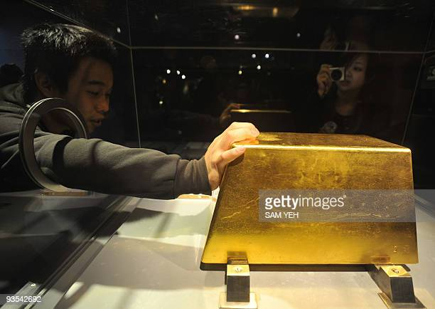 An visitor touches the world's largest solid gold brick weighing 220kg at the Jinguashi Gold Museum in Ruifang Taipei county on December 2 2009 Hong...