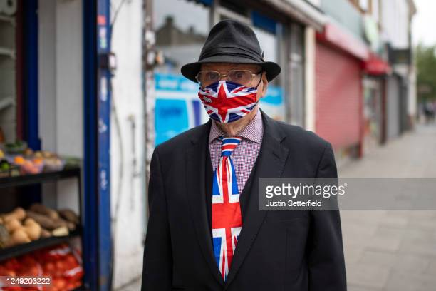 An walks down a high street in East London wearing a matching Union Jack tie and face mask on June 12, 2020 in London, England. As the British...
