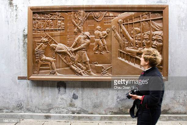 An Western visitor passes by an art work on the wall of Hoa Lo museum The museum known widely by the nickname 'Hanoi Hilton' given to it by the...