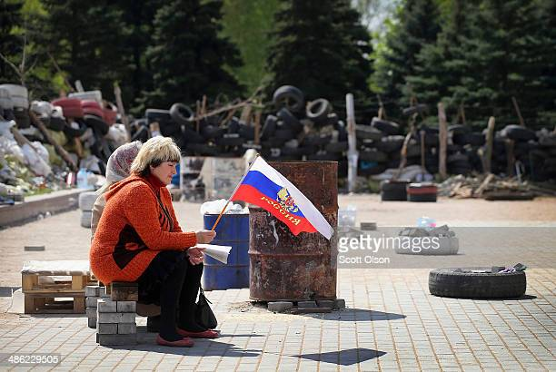 An woman holds a Russian flag as she sits next to an elderly women inside a compound created by barricades which surround the Donetsk Regional...