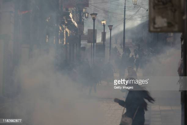 An woman runs in a tear gas cloud during a protest on November 15 2019 in La Paz Bolivia Morales flew to Mexico alleging a coup under military...