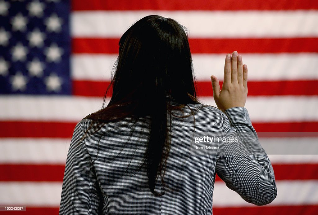 An woman takes the oath of allegiance during a naturalization ceremony at the at district office of the U.S. Citizenship and Immigration Services (USCIS) on January 28, 2013 in Newark, New Jersey. Some 38,000 immigrants became U.S. citizens at the Newark office alone in 2012.