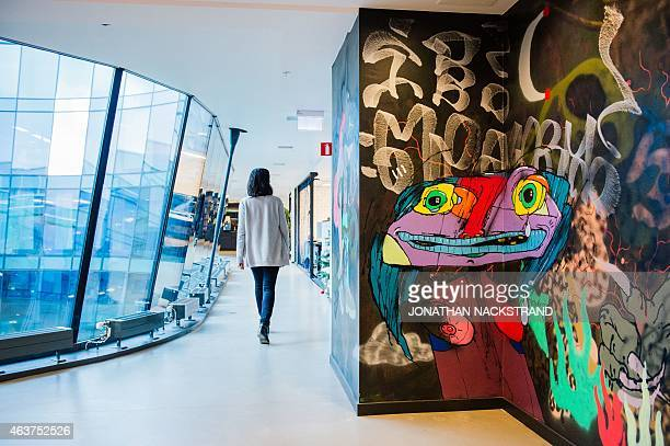 An woman walks next to a graffiti wall at Spotify headquarters in Stockholm on February 16 2015 AFP PHOTO/JONATHAN NACKSTRAND