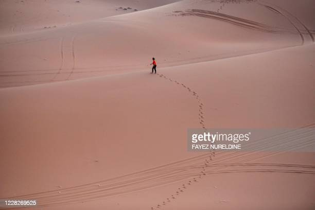 """An woman walks on the sand after surfing in the """"Saed"""" desert area, 110 Km eastern of Riyadh City, on August 29, 2020."""
