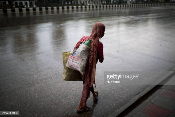 An women seen on street searching waste plastic bottle during rain in Dhaka Bangladesh on July 31 2017