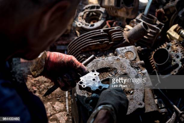 An worker tears apart a motorcycle engine at his family motorcycle scrapyard on June 7 2018 in Te Lo Village Yen Lac District Vinh Phuc Province...