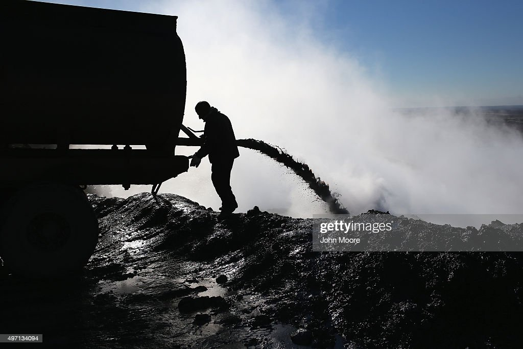 An worker unloads the dregs of oil refined into diesel fuel on November 14, 2015 near Derek, in Rojava, Syria. The predominantly Kurdish autonomous Rojava region of northern Syria had previously been supplied with pretroleum from refineries in areas now under Daesh control, so Rojavans have begun crudely processing their own reserves into diesel for domestic fuel and heating needs. The Islamic State, however, continues to pump and export millions of barrels of oil, generating vast revenues for its regional war machinery and international terrorist activities.