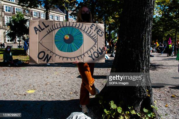 An XR activist holding a big eye placard close to a tree during the demonstration. The climate activist group, Extinction Rebellion in The...