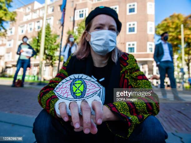 An XR activist holding a small placard with an eye during the demonstration. The climate activist group, Extinction Rebellion in The Netherlands has...