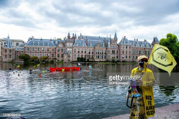 An XR activist with a flag, watching a group of activists swimming during the demonstration. The climate activist group, Extinction Rebellion in The...