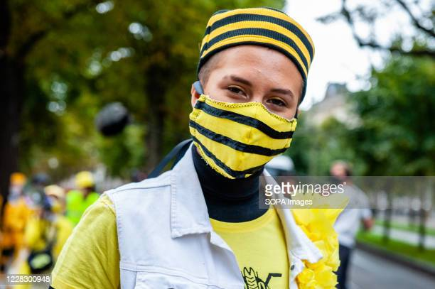 An XR model is seen wearing a bees hat and face mask during the fashion show. An 'XR fashion show' was carried out in front of the House of...