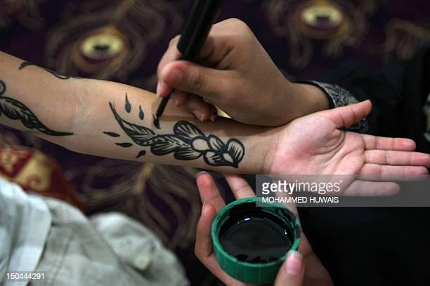 An Yemeni woman applies traditional henna designs to the arm of a girl ahead of the Muslim festivities of Eid alFitr Sanaa on August 18 2012 Muslims...