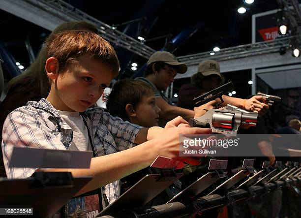 An young attendee inspects a handgun during the 2013 NRA Annual Meeting and Exhibits at the George R Brown Convention Center on May 4 2013 in Houston...