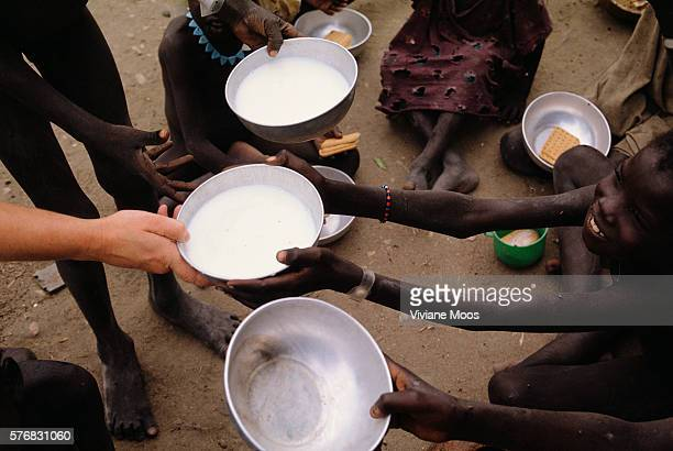 An young boy receives a bowl of milk at a feeding center in Kongor Sudan Civil war and widespread famine have ravaged Sudan for decades resulting in...