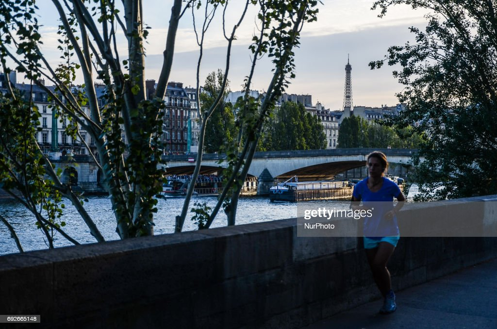 An young girl is running past the Seine river. People used the first days of the summer for walking around the French capital of Paris. The temperature of the weather is about 25 celsius degrees Paris, France on June 04, 2017