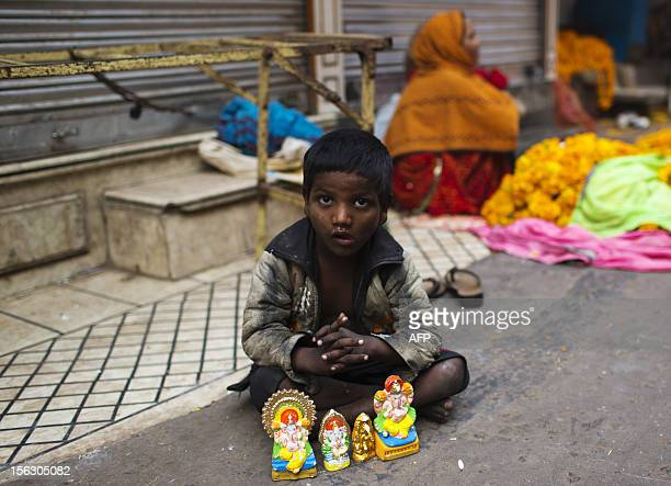 An young Indian street child looks up as he sells small Hindu effigies for the Diwali festival in the Old Quarters of New Delhi on November 13 2012...