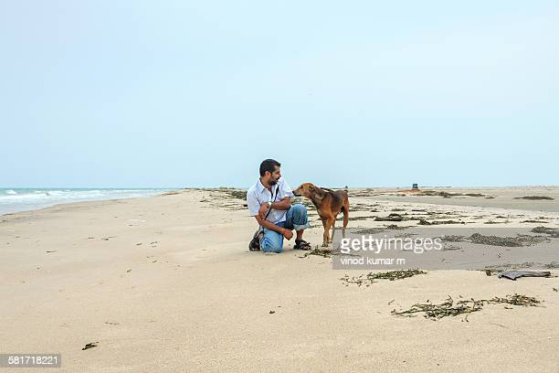 An Young Man playing with a Dog on Beach
