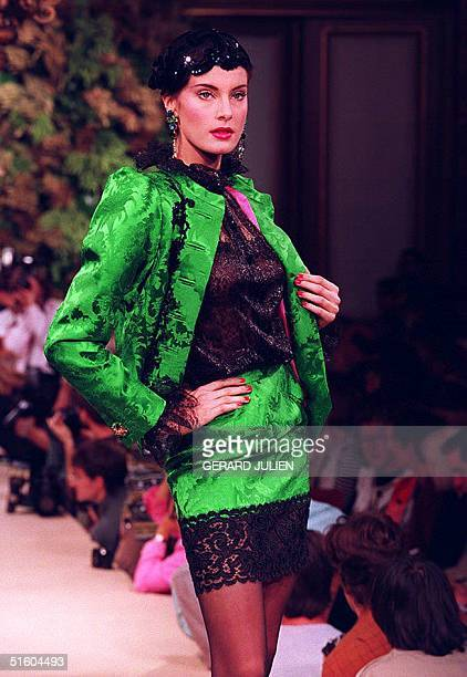 An Yves St. Laurent model shows a Chinese green damask silk suit with black lace trim, chenille embroidery and a sheer black lace blouse, during his...