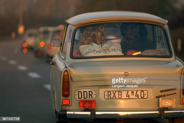 An YvesSaintLaurent shopping bag sits in the rear window of an EastGerman car driving near the airport following the shopping frenzy in West Germany...