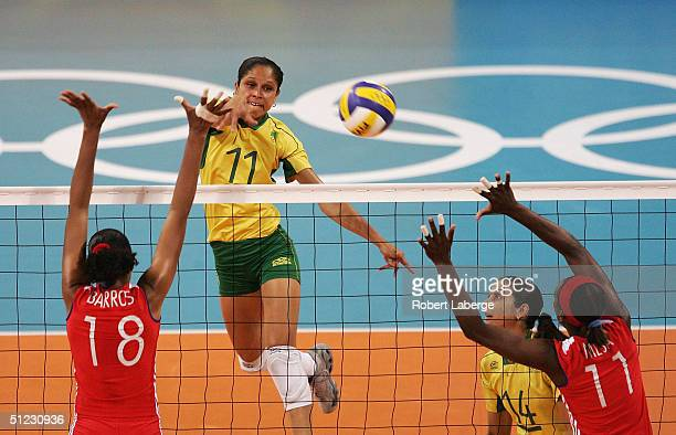Ana Chagas of Brazil spikes the ball past Zoila Barros Fernandez and Liana Mesa Luaces of Cuba in the women's indoor Volleyball bronze medal match on...