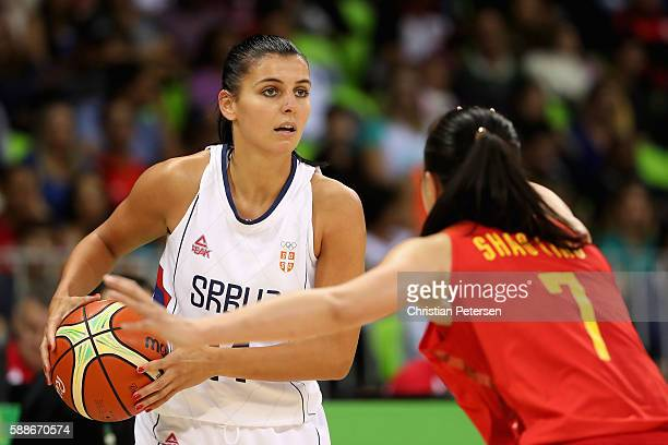 Ana Dabovic of Serbia handles the ball guarded by Ting Shao of China during the women's basketball game on Day 7 of the Rio 2016 Olympic Games at the...