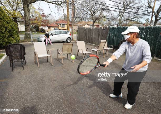 Ana Diaz a nurse at Northwell Syosset Hospital plays tennis with her husband Melanio on a makeshift court they created on the driveway of their home...